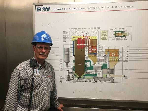 Dry Fork Station Plant Manager Tom Stalcup standing next to a lay-out of the plant in an elevator.