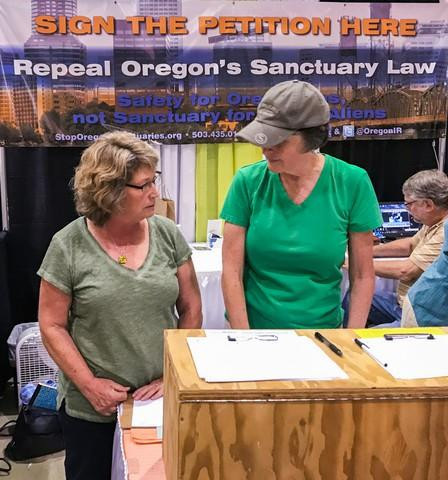 <p>In this 2017 photo, Cynthia Kendoll, left, talks with volunteers at the Oregon State Fair booth of Oregonians for Immigration Reform. The group is gathering signatures for a proposed ballot measure that seeks to overturn the state's 30-year-old sanctuary law.</p>