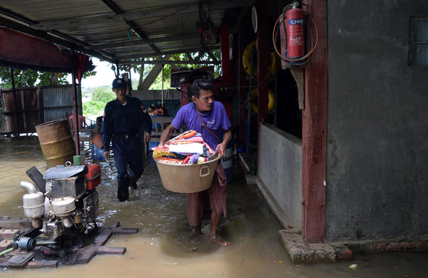 A resident evacuates with belongings from his home to escape the rising floodwaters in the Bago region in Myanmar on Wednesday.