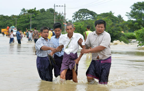 Central Myanmar residents negotiate a flooded road after waters submerged villages.