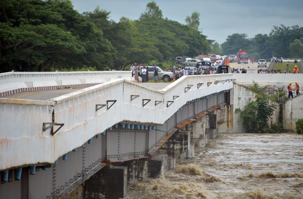 A major bridge along the highway connecting Yangon to Mandalay has been damaged by rampaging floodwaters from a failed dam.