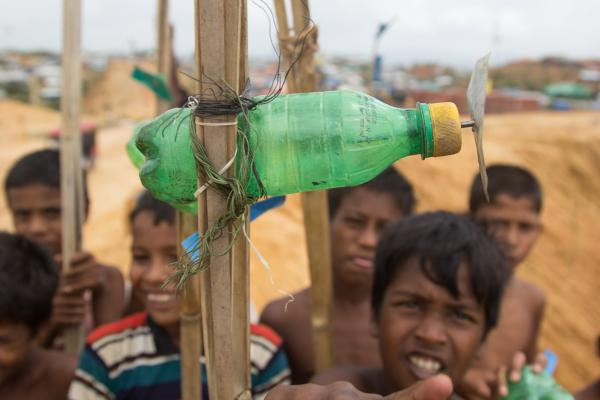 Kids in the Balukhali Rohingya refugee camp try to get the propellers on their homemade toy airplanes to spin as fast as possible.