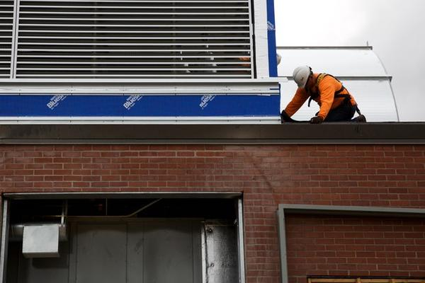 <p>A construction worker works on the roof of Harriet Tubman Middle School.</p>
