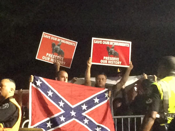"""A few dozen neo-Confederate protesters gather while a few hundred dancing demonstrators hold a """"dance party"""" at the site of the toppled Silent Sam statue at UNC- Chapel Hill on Aug. 30, 2018."""