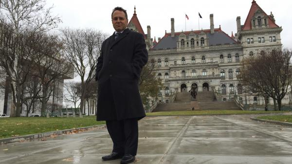 "Bruce Roter standing in front of the New York State Capitol, a place he says some would claim is ""the epicenter of all that's wrong with New York state government."""