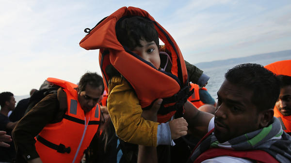 A boy is carried ashore moments after his arrival with other Syrian and Iraqi migrants on the island of Lesbos from Turkey on October 14, 2015 in Sikaminias, Greece. A recent piece in <em>Scientific American </em>highlights the connection between the Syrian refugee crisis and Syria's recent drought.