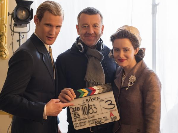 Peter Morgan (center) poses with Matt Smith, who plays Prince Philip, and Claire Foy, who plays Queen Elizabeth II, on the set of <em>The Crown.</em> Morgan also wrote the screenplays for <em>The Queen</em> and <em>Frost/Nixon.</em>