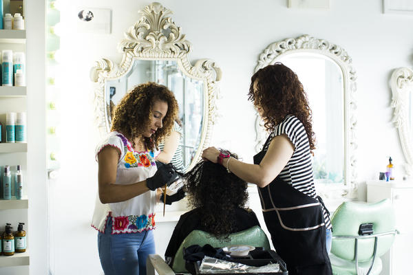 Gerlin Santos (left) and Cristina Gandia (right) dye Lisney Santiago's hair at OM Studio in San Juan.