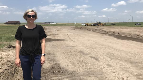 Mary Wilson, director of the local economic development office in Ogallala, Neb., visits the site of a new subdivision on the prairie north of town.