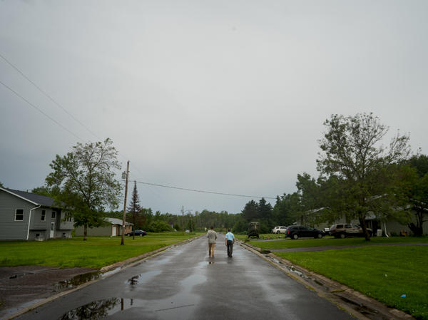 James Rees, left, and Nicholas Pinter of the University of California, Davis, gather housing data in the town of Odanah, Wis.