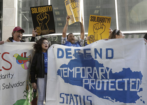 Supporters of Temporary Protected Status immigrants hold signs and cheer at a rally. Court documents released this week reveal efforts by DHS to justify ending TPS for immigrants in certain countries by showing their home countries were safe, even when other officials disagreed.