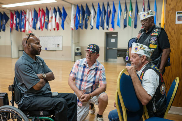 Sherman Gillums Jr., (left) chief strategy officer of AMVETS, speaks with veterans at the Heal American Veterans Town Hall in Smyrna, Tenn. AMVETS hosted the meeting to hear from service members, veterans and family members.