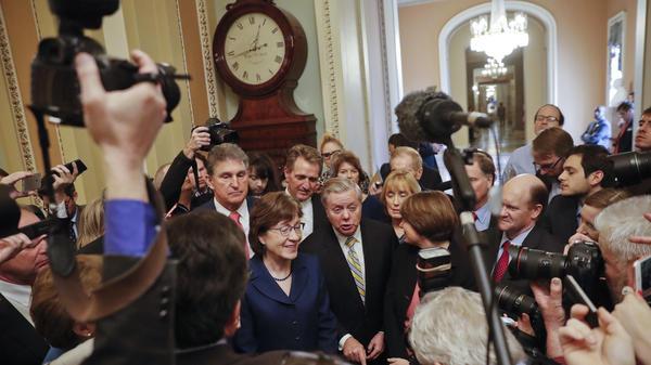 Sen. Lindsey Graham, R-S.C., speaks to members of the media outside the Senate Chamber in Washington, Jan. 22, 2018, after reaching a bipartisan agreement to advance a bill ending the government shutdown. With Graham are (L-R) Sen. Joe Manchin, D-W.Va., Sen. Susan Collins, R-Maine, Sen. Jeff Flake, R-Ariz., Sen. Lisa Murkowski, R-Alaska, Sen. Maggie Hassan, D-N.H., and Sen. Chris Coons, D-Del.