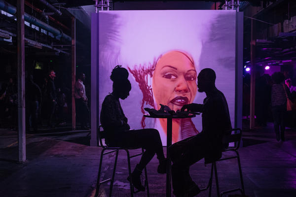 A mural illuminates an intimately lit lounge area at the Afropunk London festival in July 2017.