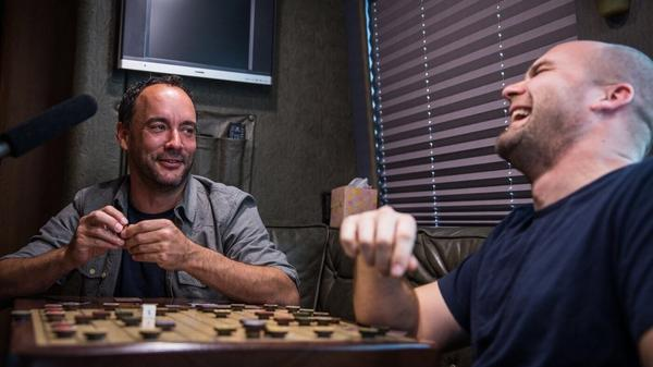 Brian Calhoun (right) makes guitars for musicians like Dave Matthews, but his newest creation is a board game called Chickapig — and he had a board custom-installed in Matthews' tour bus.