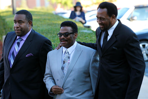 Former boxer Tommy Hearns (right) and friends head to the church for the funeral service. He was among many well-known attendees.