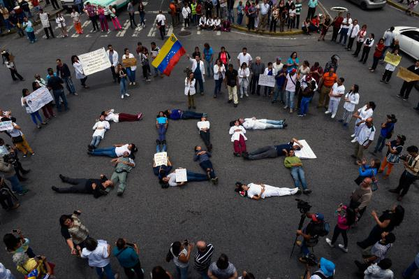 "Health workers form a human chain reading ""SOS"" during a protest for the lack of medicines, medical supplies and poor conditions in hospitals, in Caracas on Aug. 2."