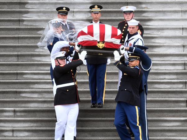 The casket of Sen. John McCain, R-Ariz., is carried down the steps of the U.S. Capitol in Washington on Saturday. The motorcade carrying the flag-draped casket paused at the Vietnam Veterans Memorial on its way to the National Cathedral.