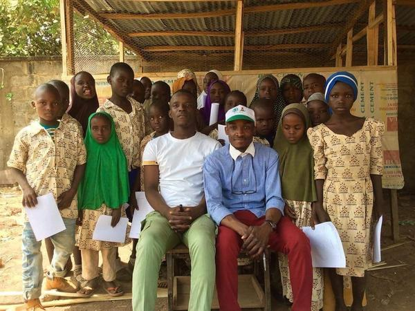 Aweofeso Adebola (in white shirt) and Ifeoluwa Ayomide (in cap) pose with some of the kids in their education program in Abuja, Nigeria.