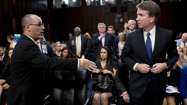 Fred Guttenberg (left), whose daughter, Jaime, was killed in the Marjory Stoneman Douglas High School shooting in Parkland, Fla., attempts to shake hands with Kavanaugh (right) as the nominee leaves for a lunch break while appearing before the Senate Judiciary Committee Tuesday.