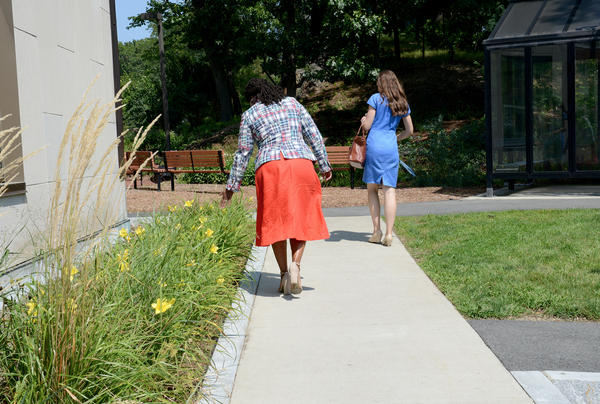 Rushing off to her next event, Pressley runs her hand along a flower bed in front of Leventhal House.