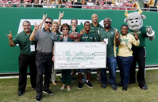 Officials from USF, the USF Black Leadership Network and the Helios Education Foundation pose with a check representing Helios' donation to the BLN at a USF football game Sept. 1.