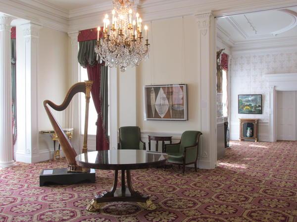 The music room with various artwork. The harp is from Lyon & Healy Harps, Chicago, 1896