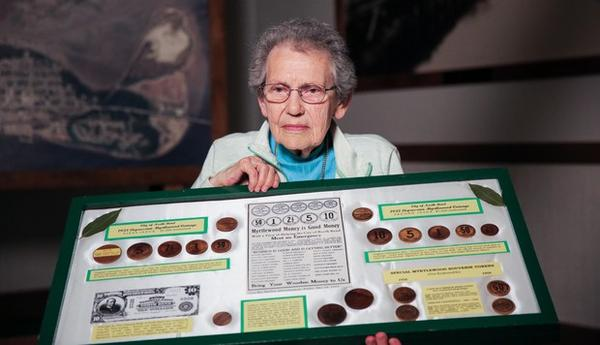 <p>Lifelong North Bend, Oregon, resident Pat Choat Pierce poses with her collection of the city's myrtlewood money. Pierce is widely regarded as the foremost expert on North Bend's wooden currency.</p>