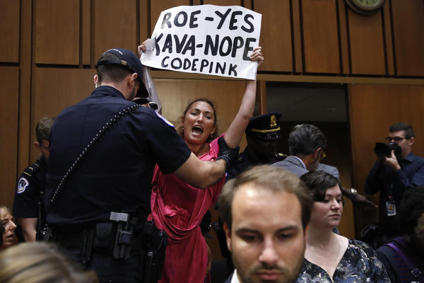 A woman stands and voices her opposition to Supreme Court nominee Brett Kavanaugh, during a Senate Judiciary Committee confirmation hearing on his nomination for Supreme Court, on Capitol Hill, Tuesday, Sept. 4, 2018, in Washington.
