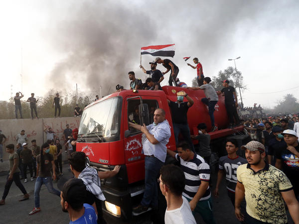 Iraqi protesters gathered outside the burned local government headquarters on Friday.