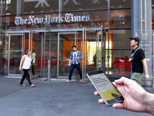"A smartphone displaying a <em>New York Times</em> op-ed piece titled ""I Am Part of the Resistance Inside the Trump Administration"" is held up in front of The New York Times building."