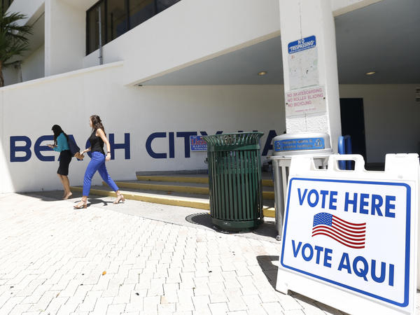 Pedestrians walk past a sign for a polling station at Miami Beach City Hall last month. On Friday, a federal judge ordered Florida officials to provide sample ballots in Spanish.