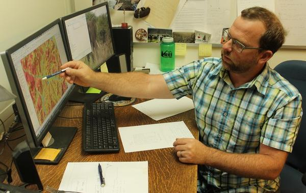 <p>Oregon State University professor Chris Dunn examines a map of the likelihood of success for fire suppression in southern Oregon. Dunn is part of a Forest Service team using data to improve decision-making and risk assessment. </p>