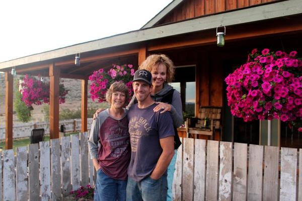 <p>Maura Hammack, left, Albert Rollins and Kelli Jo Hammack stand in front of their house outside Madras, Oregon. John Hammack, the patriarch of the family, was killed in 2013 by a burning, falling tree. </p>