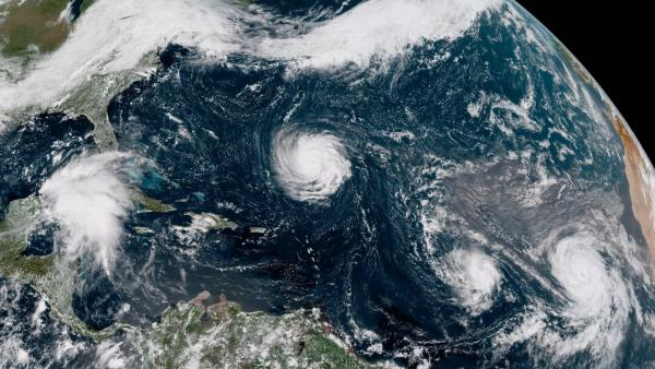 Hurricane Florence, at center, is a Category 4 storm heading for the Carolinas. To the east, hurricanes Isaac and Helene (far right) are seen in the Atlantic Ocean. To the west, a tropical disturbance has developed over the northwest Caribbean Sea.