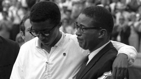 Arthur Ashe holds his trophy for the U.S. Open singles tennis championship as he stands arm-in-arm with his father, Arthur Ashe Sr., who fights back tears following his son's victory at Forest Hills, N.Y., Sept. 9, 1968. The younger Ashe defeated Holland's Tom Okker in five sets.
