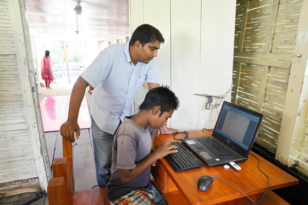 Mohammad Saiful Islam coaches a kid how to use a computer in a floating library run by the nonprofit group Shidhulai Swanirvar Sangstha.