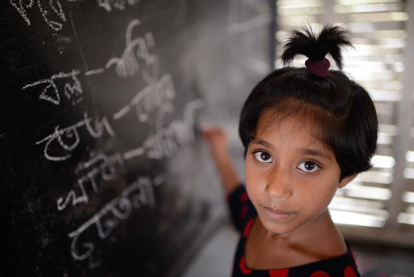Rakhu Khatun, age 9, writes on the blackboard, which sits in front of the boat's engine.