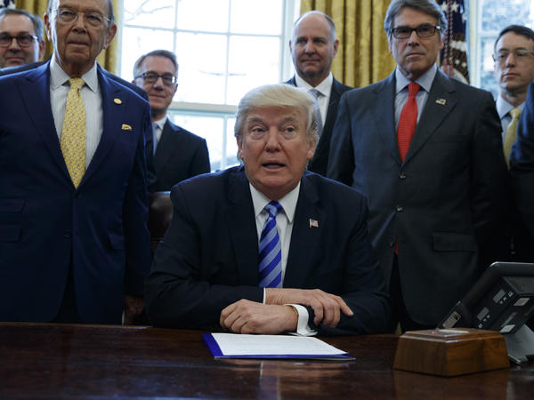 President Trump, flanked by Commerce Secretary Wilbur Ross (left) and Energy Secretary Rick Perry (right), announces the approval of a permit to build the Keystone XL pipeline, in March 2017.