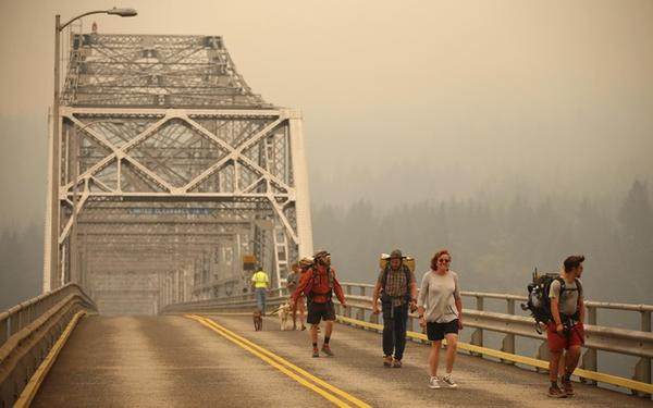 <p>Pedestrians walk off the Bridge of the Gods, which spans the Columbia River between Washington and Oregon, as smoke from the Eagle Creek Fire obscures the Oregon hills in the background near Stevenson, Washington, Wednesday, Sept. 6, 2017.</p>
