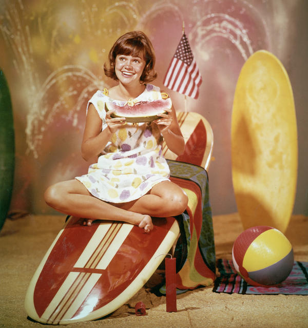 "Field sits on a surfboard in a promotional portrait for the 1965 television series <em>Gidget.</em> ""I represented the 'girl next door,' the 'all-American girl,' "" she says."