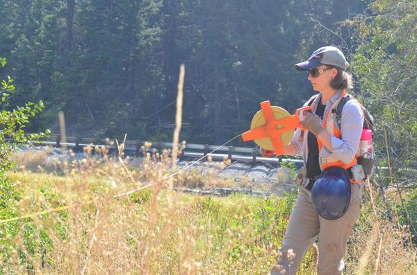 <p>Rebecca Wassel, a biologist who helped design the project,helps mark where the creek is going to run after the culvert gets replaced.</p>