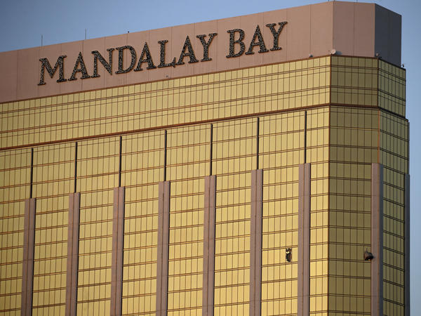 On Oct. 2, 2017, drapes billow out of broken windows at the Mandalay Bay resort on the Las Vegas Strip, following a deadly shooting at a music festival. On Tuesday, the company that owns the hotel offered to make a $500 charitable donation for victims who authorize their lawyers to accept legal notice of the company's lawsuit.