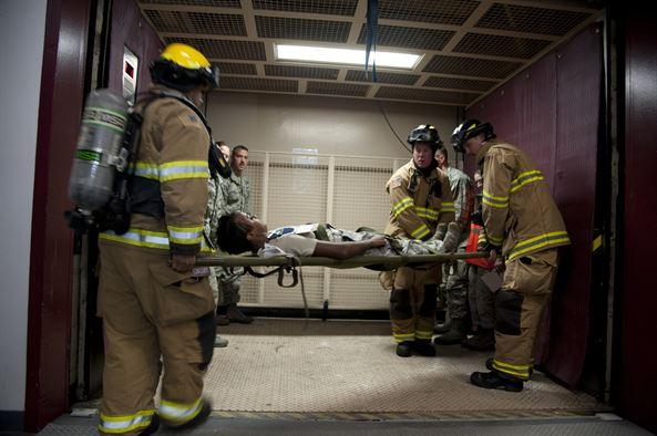 First responders carry an injured person on a stretcher.