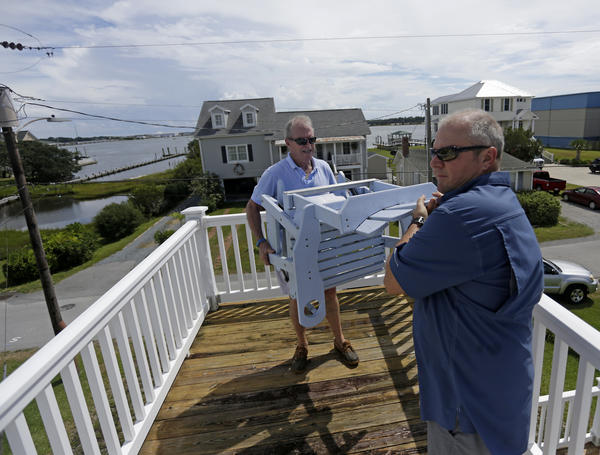Frank Weaver, left, and Tony Weaver remove chair from the third story of a home, Tuesday, Sept. 11, 2018, in Swansboro, N.C., as they prepare for Hurricane Florence.