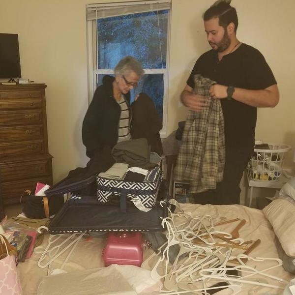 Juan Rojas, right, and his 69-year-old mother Margarita Rivera, left, pack clothing into suitcases before storing them in their closet to protect them from any water damage that might occur in the storm.