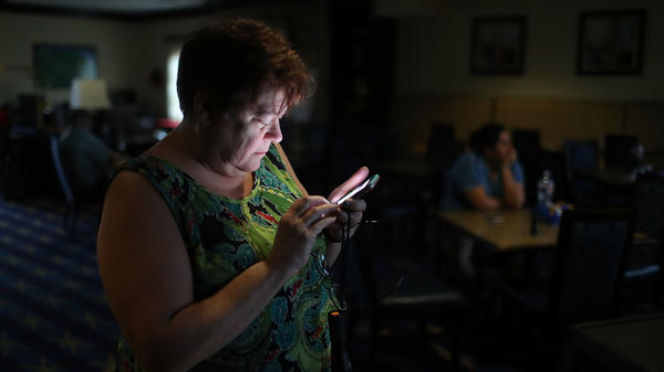 Amy Currin watches the weather news on her cell phone after the power went out at the hotel where she was taking shelter from Hurricane Harvey last August.