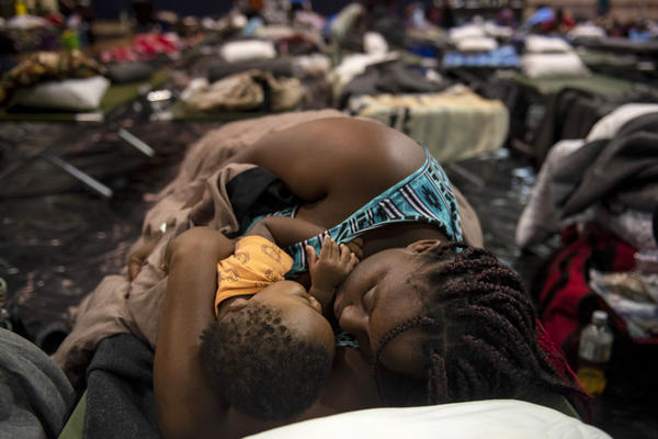 A woman holding a child sleeps at Southeast Raleigh High School in Raleigh, N.C., on Wednesday after being evacuated from her home ahead of Hurricane Florence.