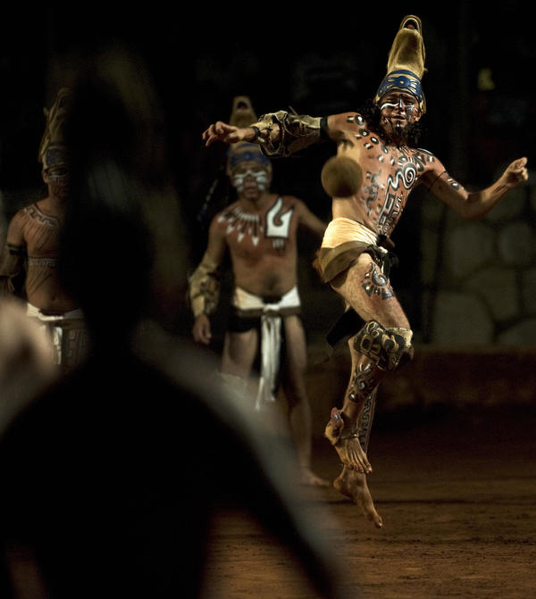 A man in pre-Hispanic dress plays a traditional indigenous ballgame at Mexico's Xcaret theme park.