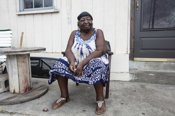 Georgia Ramson, 75, sits in front of her house and talks to neighbors in the Northside neighborhood of Wilmington, N.C. Ramson says she is not worried about the storm because she has seen many hurricanes hit the area in her lifetime.